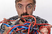 Cable guy making a face.  The scene is situated in a studio environment in front of a black background. The picture is taken with Sony A7 III camera