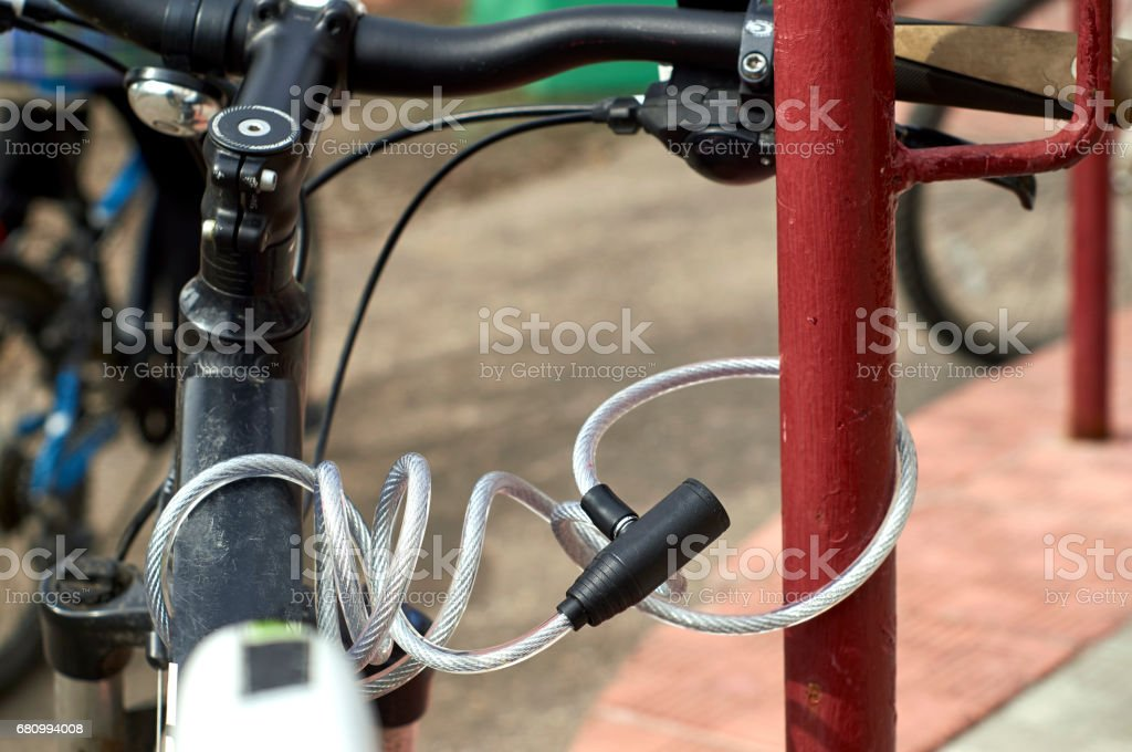 Cable security lock blocking bicycle in the street royalty-free stock photo