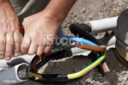 Electrician making cable splice. Construction job side.