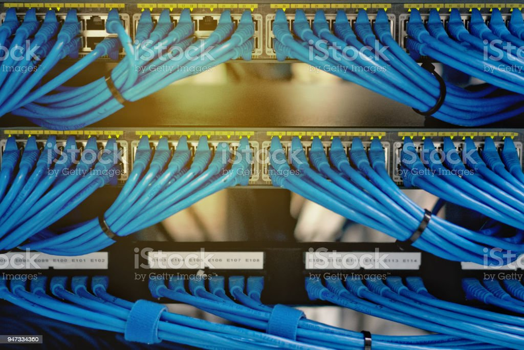 LAN cable wiring and networking in the network or server rack in the data center. stock photo