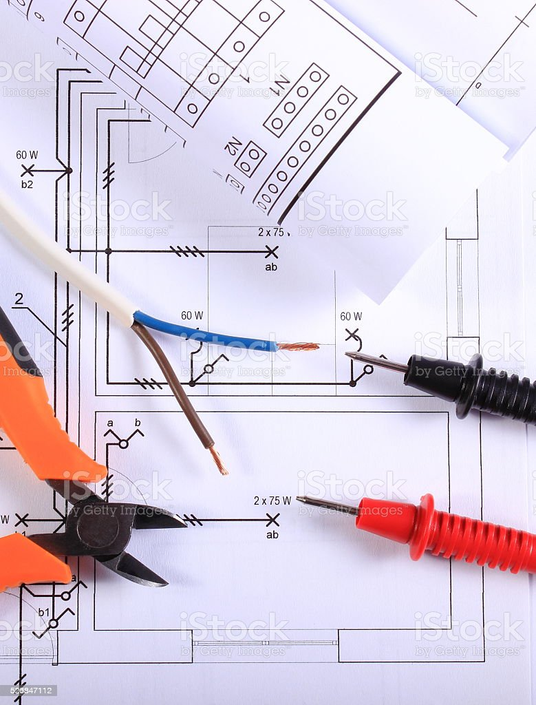 Cables of multimeter, pliers, electric wire and construction drawing stock photo