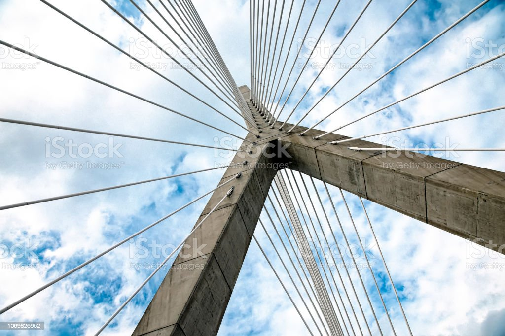 cable-stayed bridge against the blue sky with white clouds stock photo