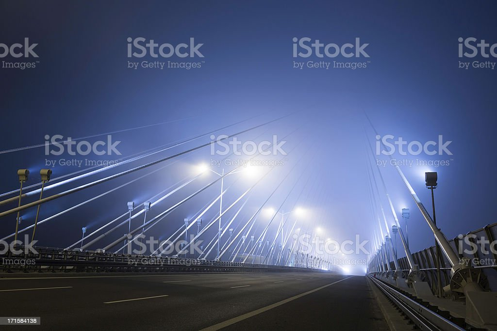 cable-stayed bridge at foggy night royalty-free stock photo