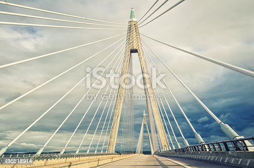 Driving thru cable-stayed bridge, view of suspension cables on vertical suspenders from road