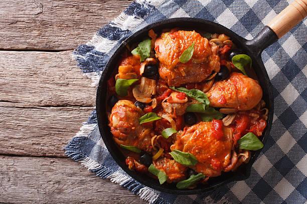 cacciatori chicken with mushrooms in a pan. horizontal top view - paprika hähnchen stock-fotos und bilder