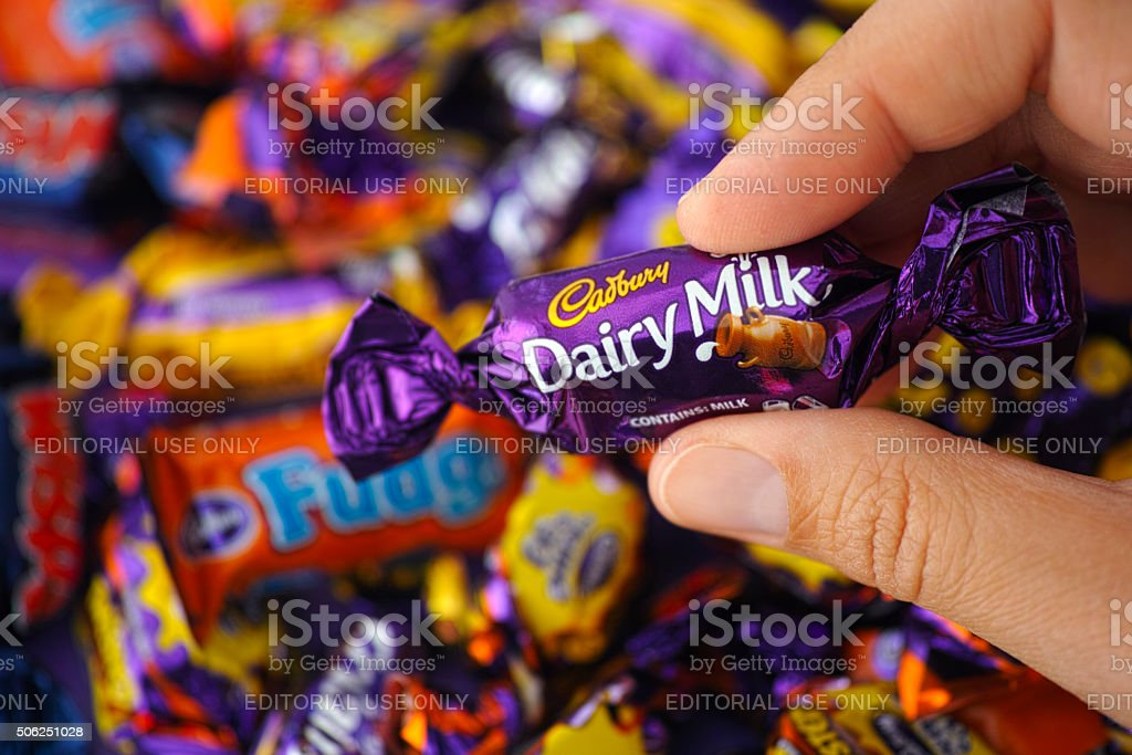 Cadbury Dairy Milk candy in womans hand stock photo