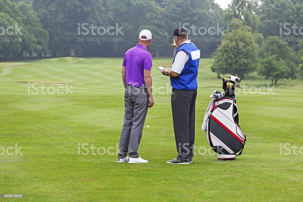 Caddy pointing out a hazard to golfer stock photo