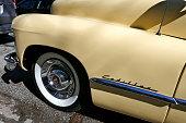 Detail, Close-up of tire, rim, fender,trademark, logo, bumper,taillight, break light, grille, hood ornament, wheels, mirror,steering wheel, dashboard