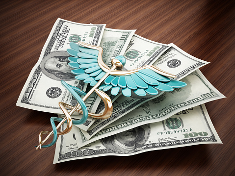 Caduceus on dollar pile standing on the table. Medical expenses concept.