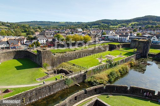 Caerphilly, Wales, UK: September 23, 2017: View from the battlements of Caerphilly Castle of the town of and the surrounding moat. Families enjoy a day out in the grounds.