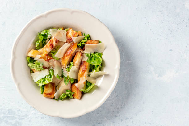 Caesar salad. Grilled chicken breast slices, green romaine salad leaves, croutons and parmesan, the classic recipe on a white marble background with a place for text stock photo