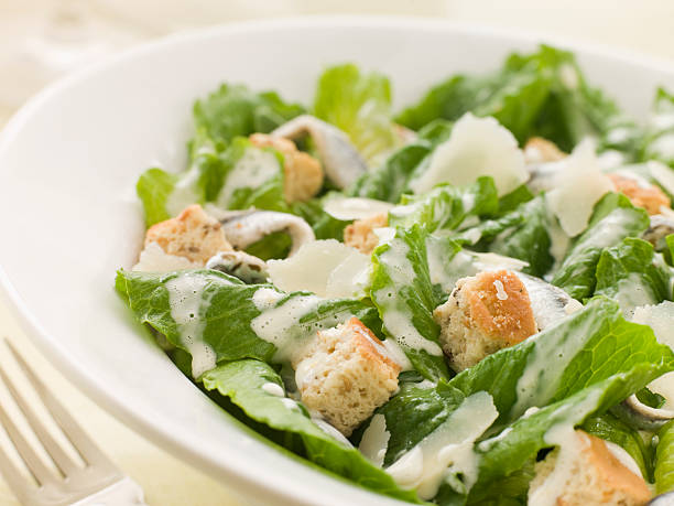 A Caesar salad in a white ceramic bowl Bowl of Caesar Salad With Fork salad dressing stock pictures, royalty-free photos & images