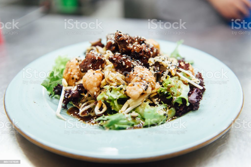 Caesar salad in a white plate on a metal surface royalty-free stock photo