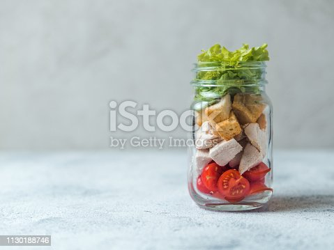 Caesar salad in glass mason jar on gray background. Copy space for text. Homemade healthy caesar salad layered in jar. Healthy food and diet concept, idea, recipe.