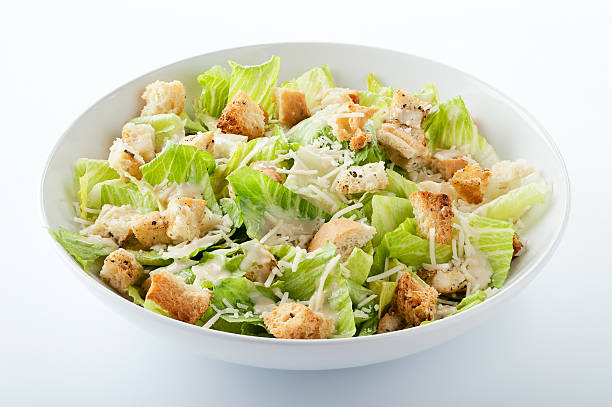 """Caesar Salad """"SEVERAL MORE IN THIS SERIES. Closeup of a fresh caesar salad, with romaine lettuce hearts, croutons, parmesan cheese and dressing.  Isolated on white with clipping path.NB:  Clipping path might be available only for the largest size.  If the clipping path is important to you, please contact iStockphoto Support to find out their current policy for image sizes that include clipping paths."""" romaine lettuce stock pictures, royalty-free photos & images"""