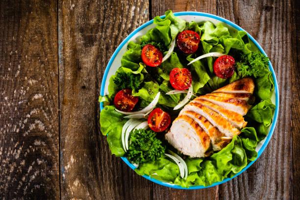 Caesar Salat - Gemüsesalat mit gebratenem Hühnerfleisch auf Holzhintergrund – Foto