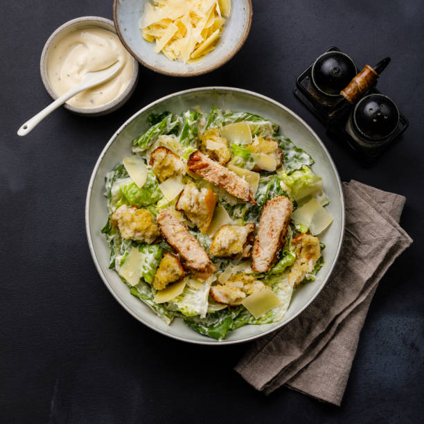 Caesar salad with Chicken breast meat on dark background stock photo