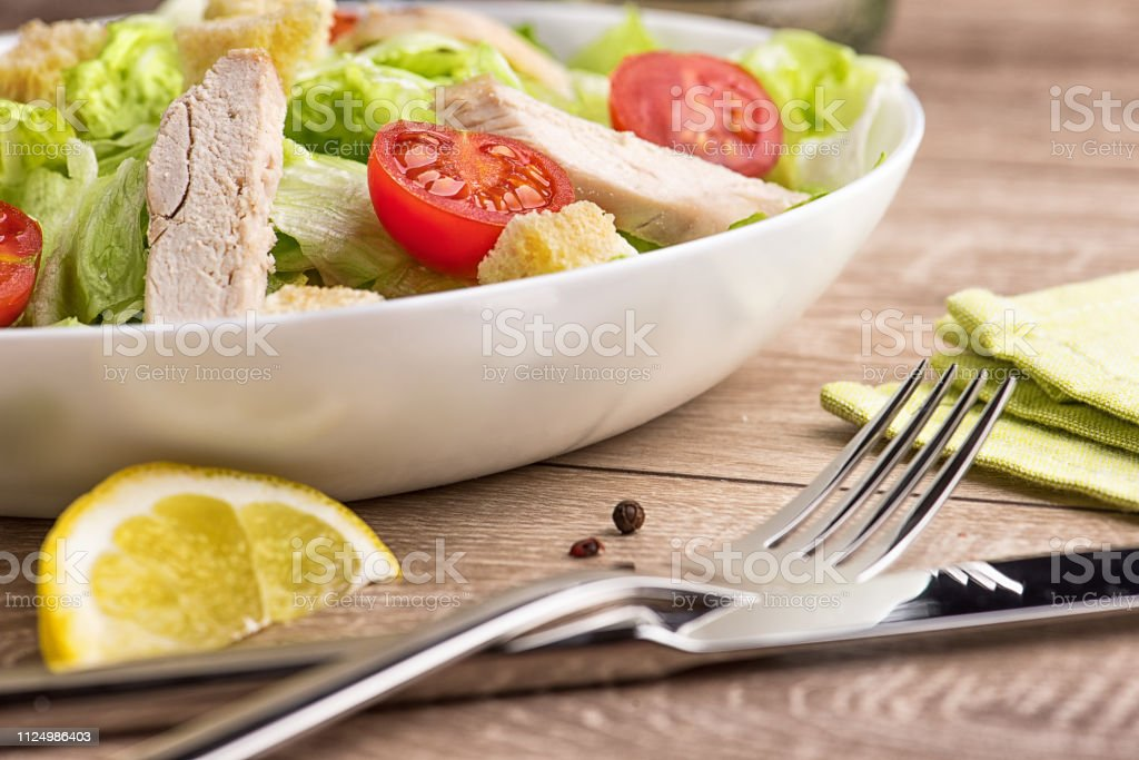 Caesar salad with chicken on a light natural table with cutlery.