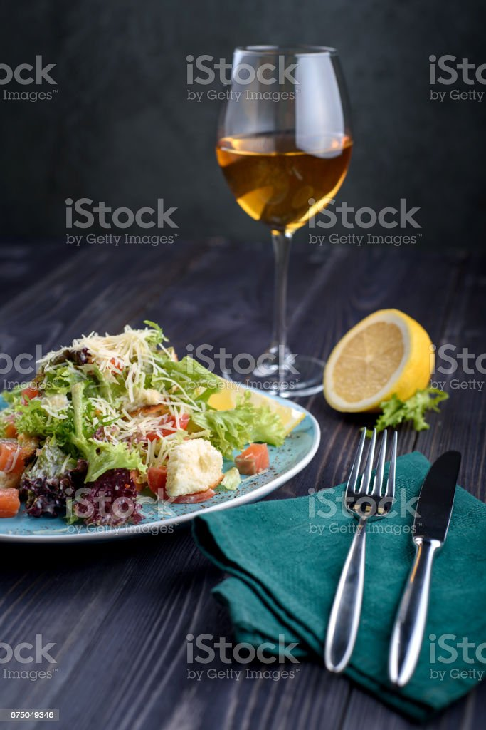 Caesar salad with salmon in a blue plate on a wooden table and a glass of wine stock photo