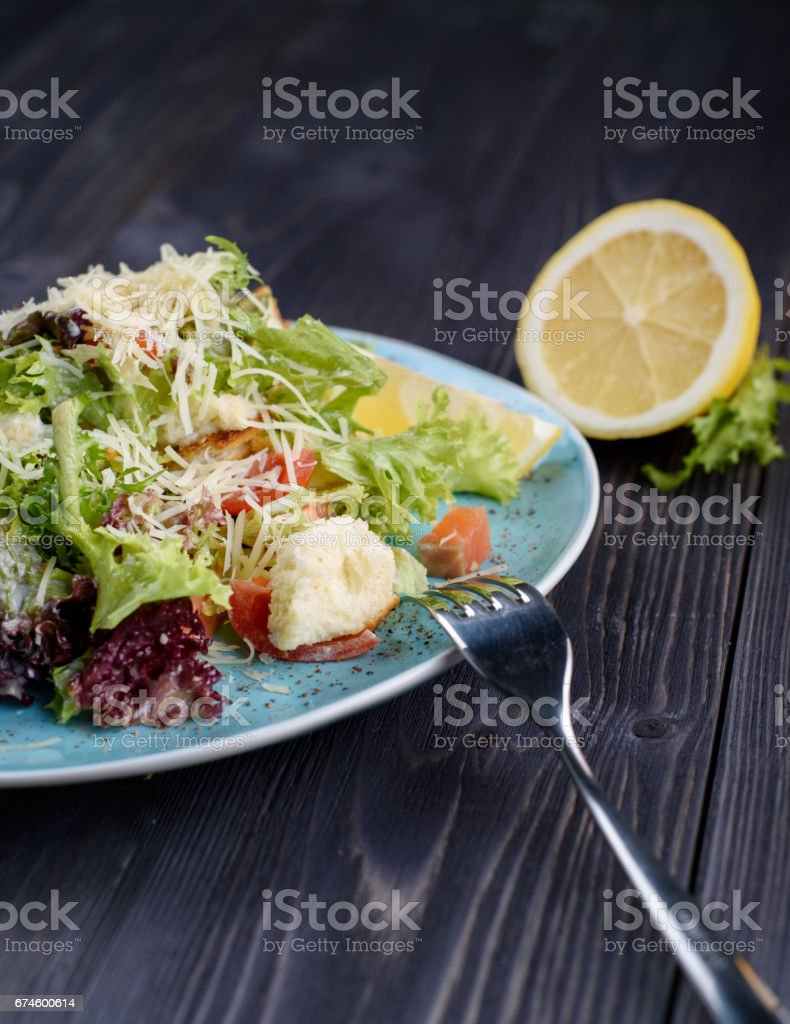Caesar salad with salmon in a blue plate on a wooden table near the lemon stock photo