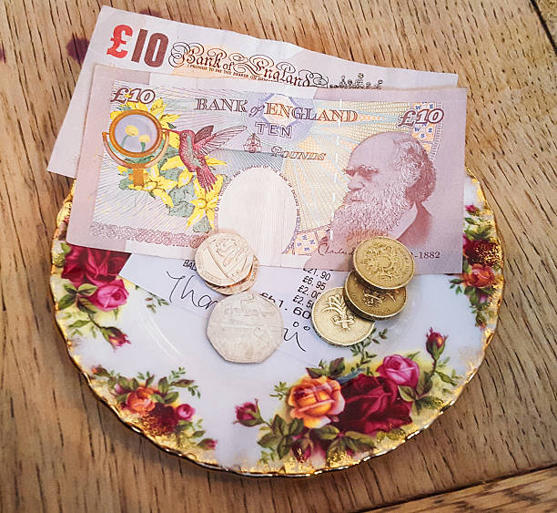 Cafe bill payment and tip Payment and a tip left in a British cafe, on an antique saucer. ten pound note stock pictures, royalty-free photos & images