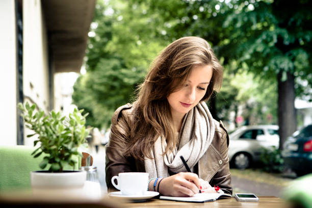 cafe culture: cheerful young woman sitting in café, handwriting stock photo