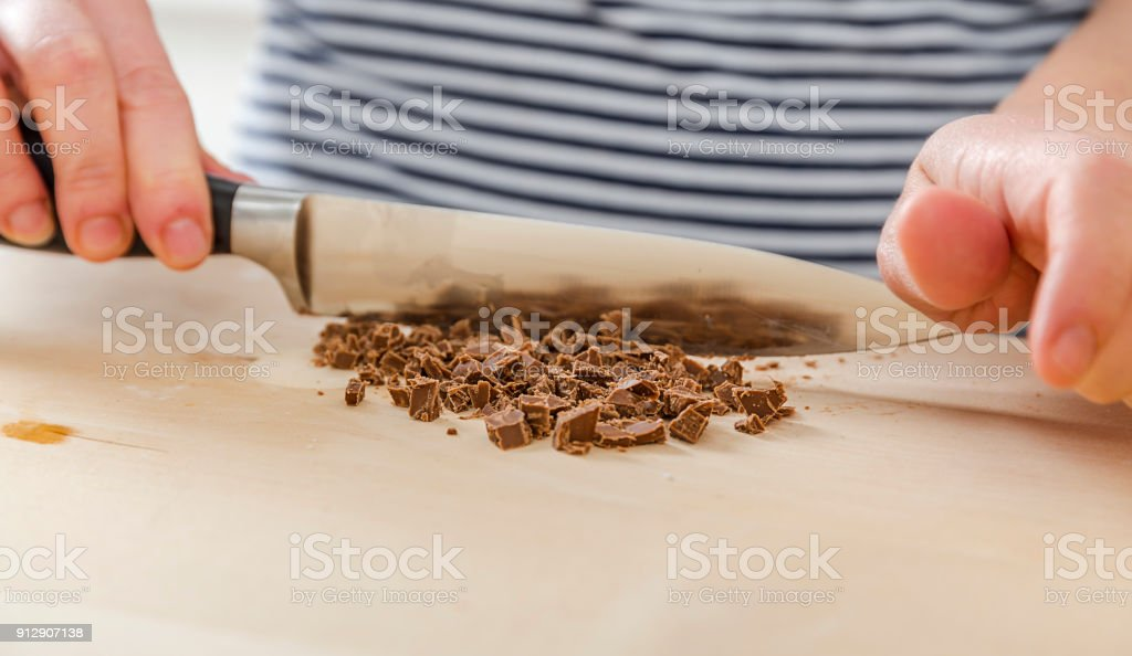 Cafe employee cuts the chocolate into small pieces. Woman prepares delicious, healthy cookies from spelt flour, oatmeal and chocolate stock photo