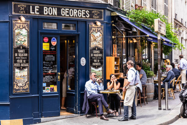 Cafe Le Bon Georges. Paris, France Paris, France - June 16, 2017: The charming Cafe Le Bon Georges. Parisians and tourists enjoy food and drinks at the street french cafe. french culture stock pictures, royalty-free photos & images