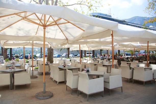 cafe on the open air under the white umbrellas of kotor, montenegro. - sonnenschirm terrasse stock-fotos und bilder