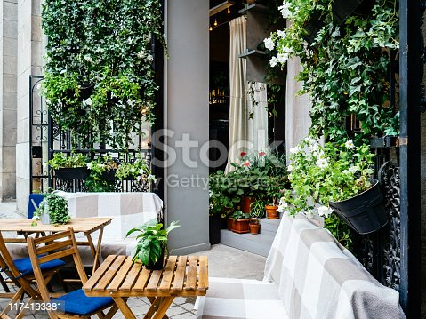 Cafe on the street decorated with flowers. Sofa, chairs and table for visitors. Pleasant atmosphere