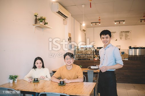 cafe owner barista serving cake dessert  to an asian chinese couple in his cafe