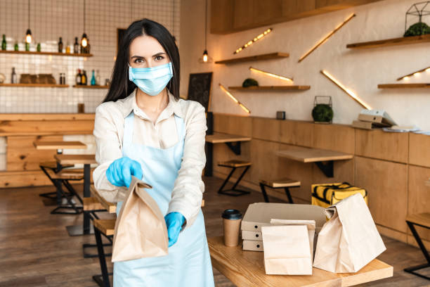 Cafe owner in medical mask showing paper bag and looking at camera near table with disposable cup of coffee and boxes stock photo