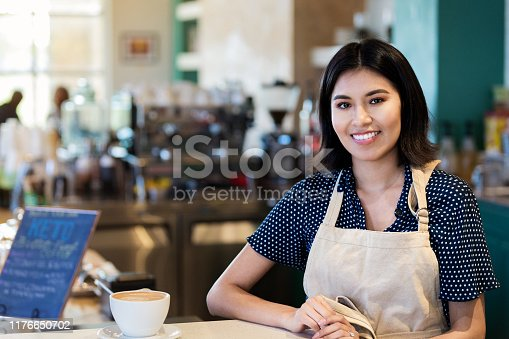 The attractive female cafe owner poses for a photo by a hot coffee in a cup and saucer that she has just set on the counter.