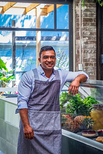 Male cafe owner smiling while leaning on glass display cabinet, outdoor ara behind window: male, Pacific Islander ethnicity