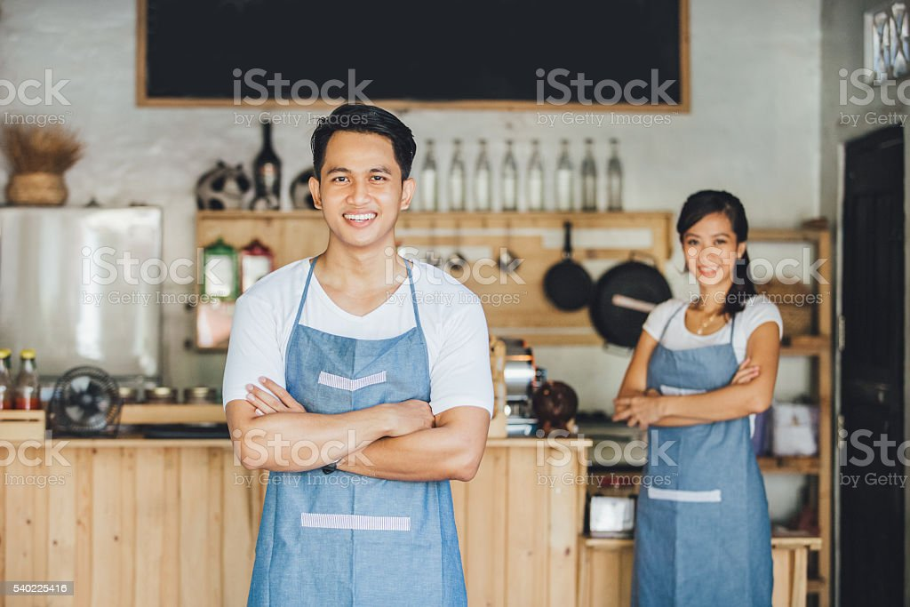 cafe owner standing with crossed arms stock photo