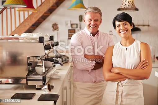 istock Cafe owners standing smiling to camera 473909220