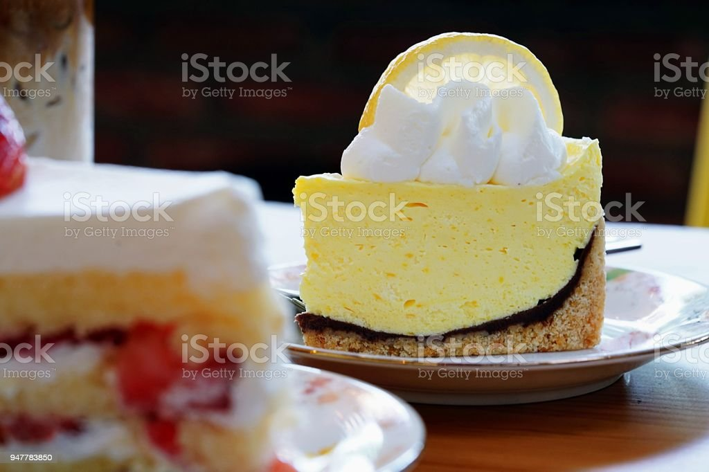 A cafe Scene for background. Two delicious cakes on wooden table, close up lemon meringue pie topped with a large fresh slice Lemon placed - fotografia de stock