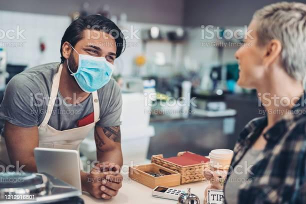 Cafe worker with protective face mask talking to a client picture id1212916801?b=1&k=6&m=1212916801&s=612x612&h=naljmdgesaw7 f6amuetfvdzlvi4xw5dbzu1szcr4 w=