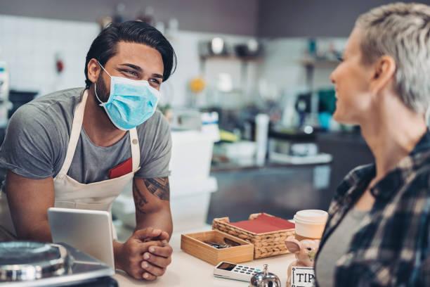 Cafe-Arbeiter mit schützender Gesichtsmaske im Gespräch mit einem Kunden – Foto