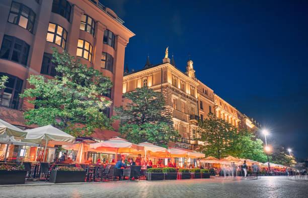 cafés und restaurants bei nacht in krakau, polen - fassadenschnitt stock-fotos und bilder