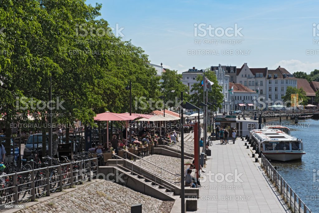 cafes with tourists on the bank of the trave river in the old town of lubeck, germany zbiór zdjęć royalty-free