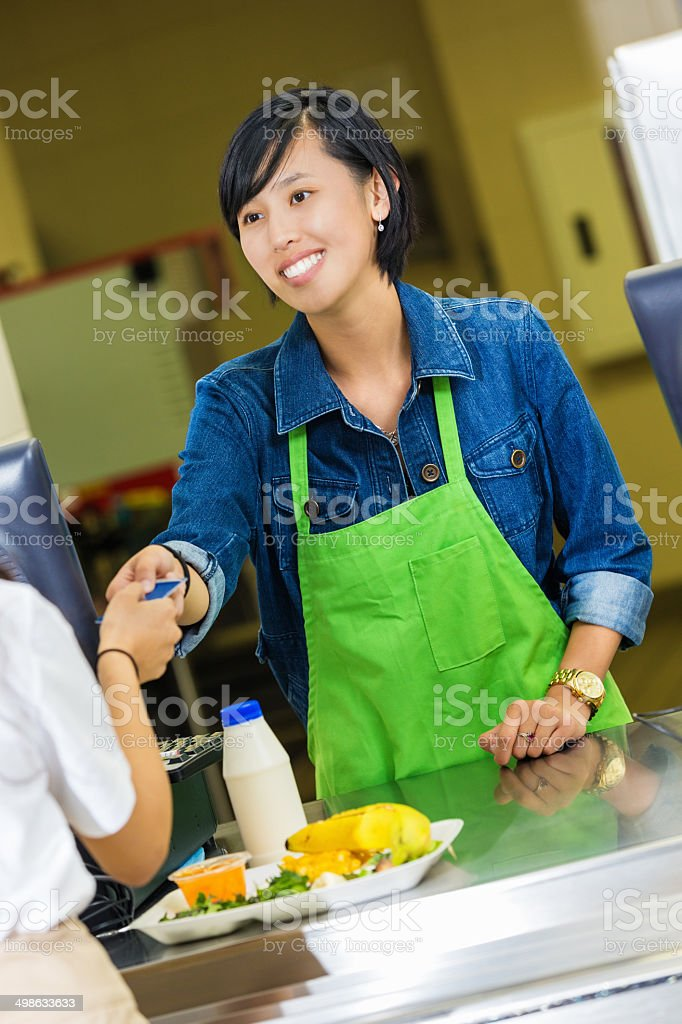 Cafeteria worker accepting credit card payment for student's meal stock photo