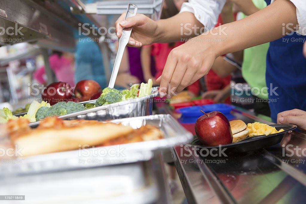 Cafeteria worker helping elementary students select food in lunch line stock photo