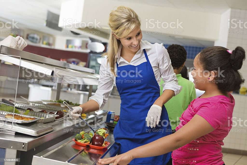 Cafeteria worker helping students make healthy choices in lunch line stock photo