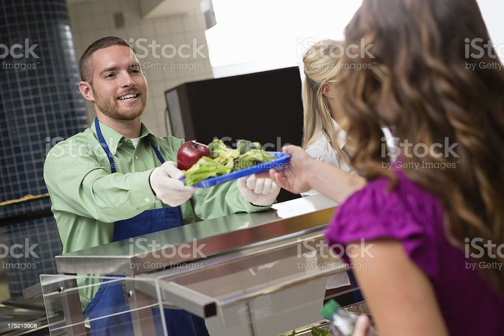 Cafeteria worker serving food to student in school lunch line stock photo
