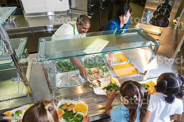Cafeteria worker serving trays of healthy food to children picture id498532103?b=1&k=6&m=498532103&s=612x612&h=qf7dbaybcas2ra9pwcelbfn1hmxfrywka7d5f2ixjik=