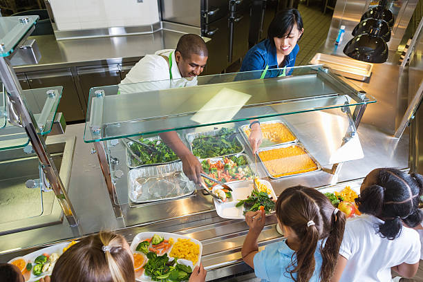 Cafeteria worker serving trays of healthy food to children stock photo