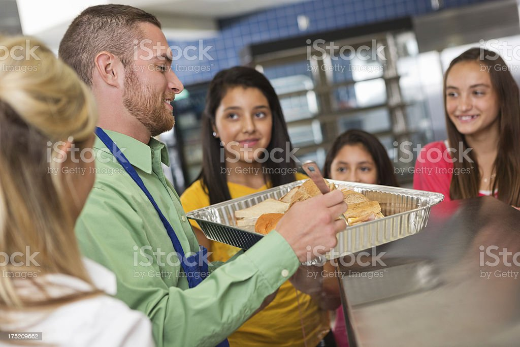 Cafeteria workers serving food to students in lunch line royalty-free stock photo