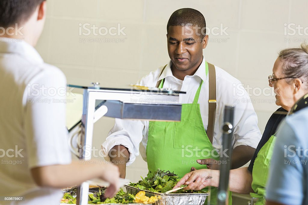 Cafeteria workers serving healthy food to students in lunch line stock photo