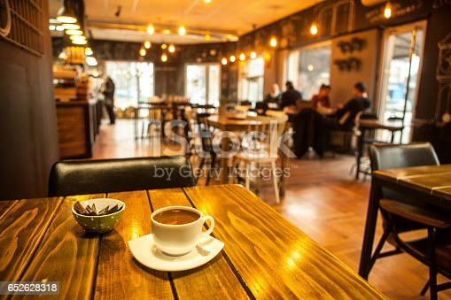Cup of caffee on table with blurred bar restaurant cafe interior background